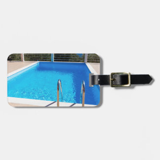 Blue swimming pool with steps at sea luggage tag