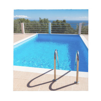 Blue swimming pool with steps at sea notepad