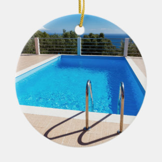 Blue swimming pool with steps at sea round ceramic ornament