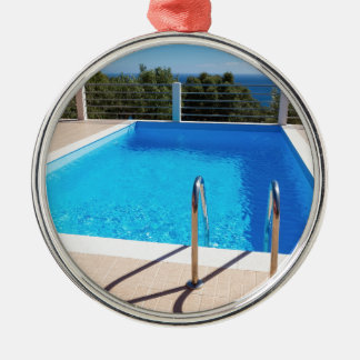 Blue swimming pool with steps at sea Silver-Colored round ornament