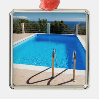 Blue swimming pool with steps at sea Silver-Colored square ornament