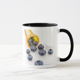 Blueberries spilling from prescription bottle mug