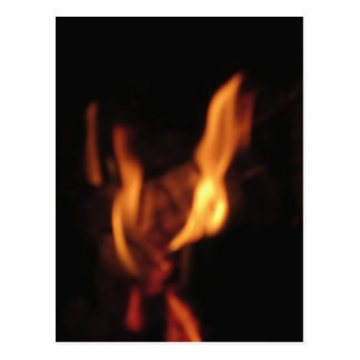 Blurred flames in a burning fireplace on black postcard