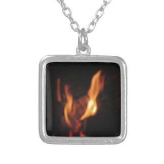 Blurred flames in a burning fireplace on black silver plated necklace