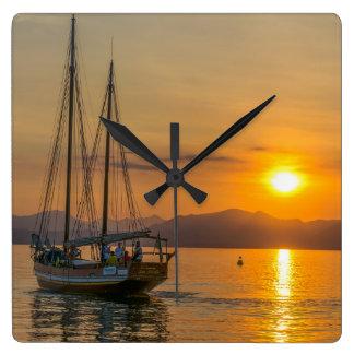 Boat at sunset square wall clock