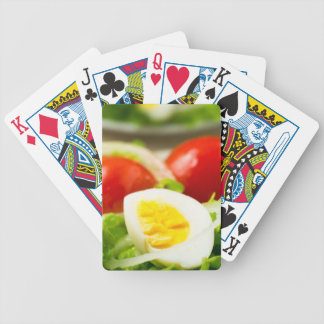 Boiled egg on a plate with lettuce, onions bicycle playing cards