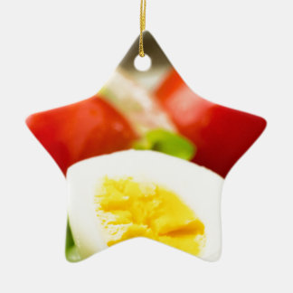 Boiled egg on a plate with lettuce, onions ceramic star ornament