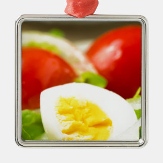 Boiled egg on a plate with lettuce, onions metal ornament