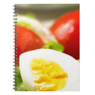 Boiled egg on a plate with lettuce, onions notebook