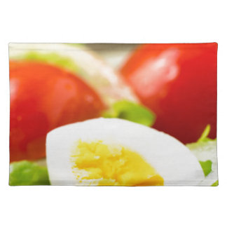 Boiled egg on a plate with lettuce, onions placemat