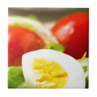 Boiled egg on a plate with lettuce, onions tile