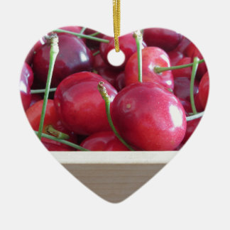 Border of fresh cherries on wooden background ceramic heart ornament