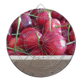 Border of fresh cherries on wooden background dartboard
