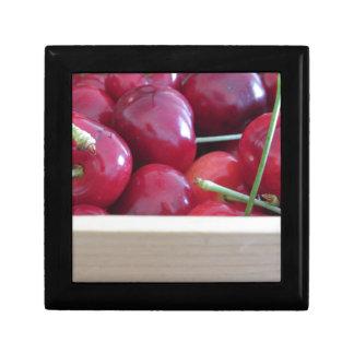 Border of fresh cherries on wooden background gift box