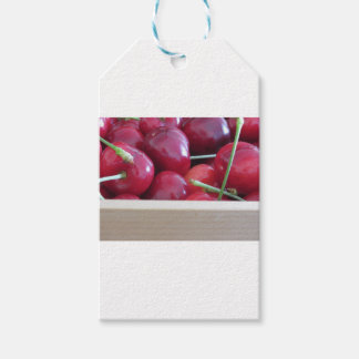 Border of fresh cherries on wooden background gift tags