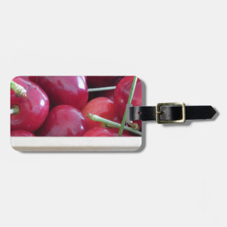 Border of fresh cherries on wooden background luggage tag