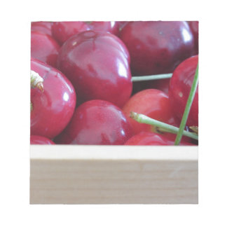 Border of fresh cherries on wooden background notepads