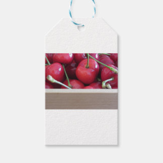 Border of fresh cherries on wooden background pack of gift tags