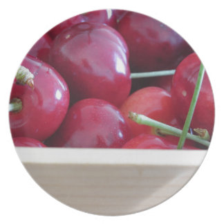 Border of fresh cherries on wooden background party plates