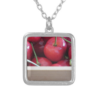 Border of fresh cherries on wooden background silver plated necklace