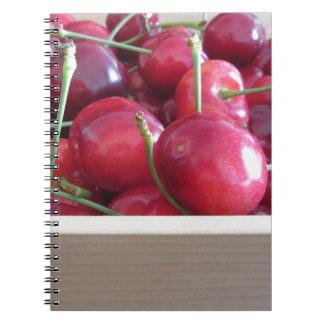Border of fresh cherries on wooden background spiral notebook