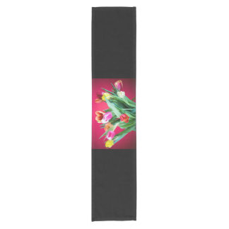 Bouquet of tulips on red short table runner