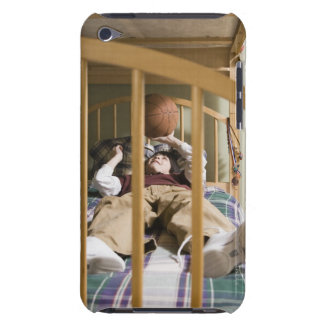 Boy (11-13) lying on bed, playing with iPod Case-Mate cases