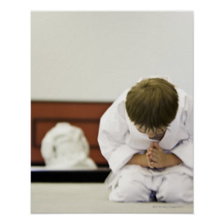 Boy (4-5 years) wearing karate outfit bowing, poster