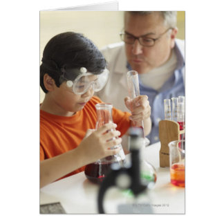 Boy (6-7) and teacher in chemistry class greeting card