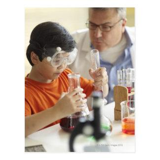 Boy (6-7) and teacher in chemistry class postcard