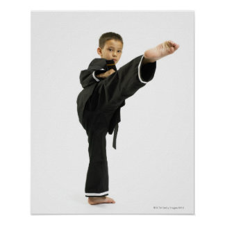 Boy (6-8) in karate outfit kicking poster