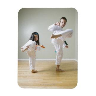 Boy and girl (4-9) practising Taekwondo kicks Rectangular Photo Magnet