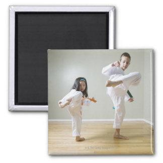 Boy and girl (4-9) practising Taekwondo kicks Square Magnet