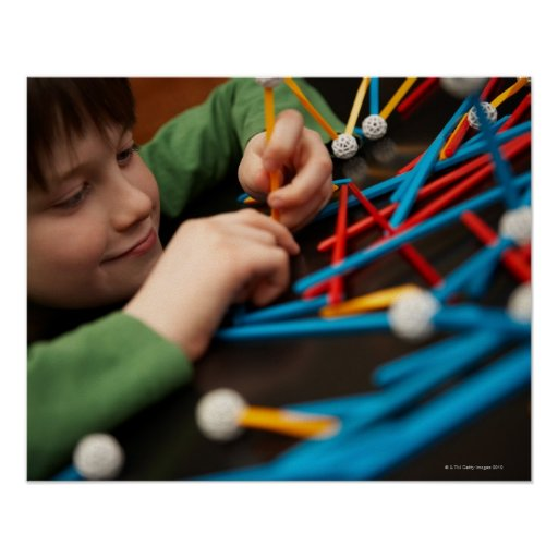 Boy connecting molecules for science project posters