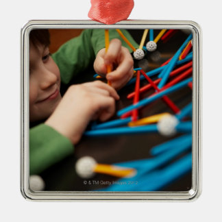 Boy connecting molecules for science project Silver-Colored square ornament