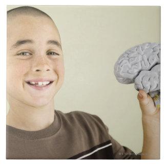 Boy holding human brain model ceramic tile