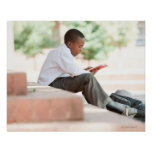 Boy reading on steps outside school, poster