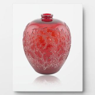 Bright red Art Deco glass vase with holly leaves. Plaque