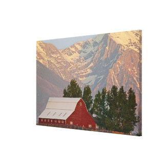 Bright red barn against Mission Mountains in Canvas Print