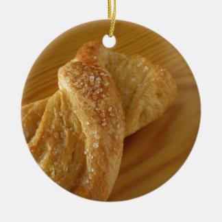 Brioche on a wooden table with granulated sugar ceramic ornament