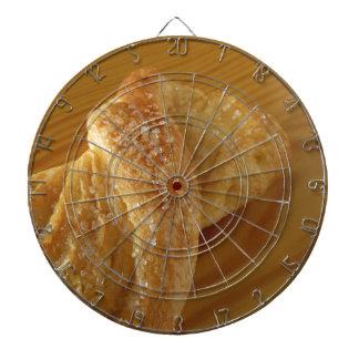 Brioche on a wooden table with granulated sugar dartboard
