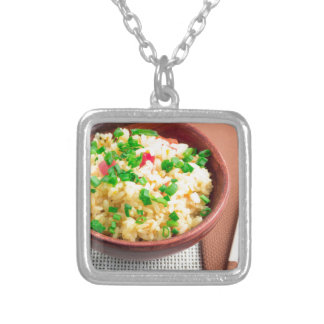 Brown bowl with a portion of cooked rice silver plated necklace