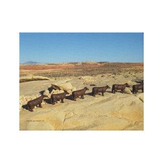 brown cows walking in desert canvas print