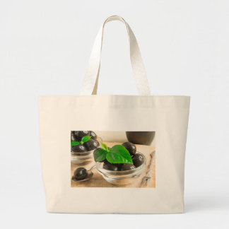 Brown pickled olives in a transparent cups large tote bag