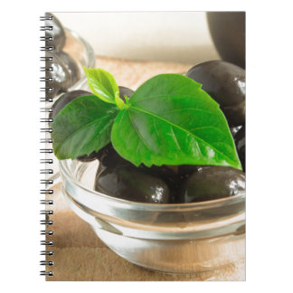 Brown pickled olives in a transparent cups notebook
