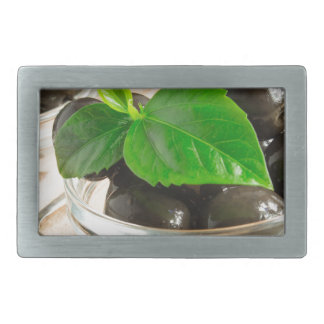 Brown pickled olives in a transparent cups rectangular belt buckle