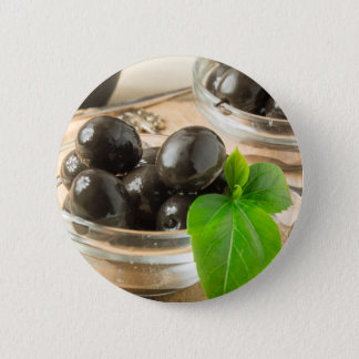 Brown pickled olives on the old wooden background 2 inch round button