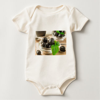 Brown pickled olives on the old wooden background baby bodysuit