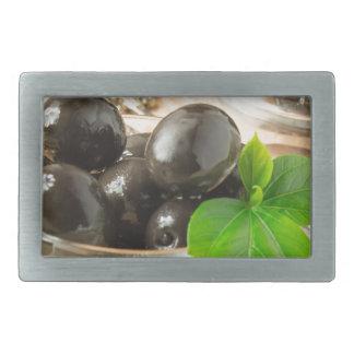 Brown pickled olives on the old wooden background belt buckle