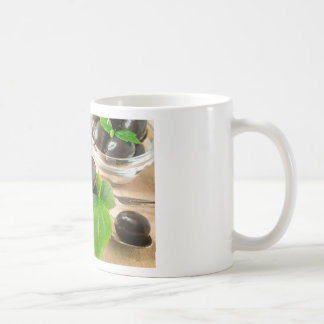 Brown pickled olives on the old wooden background coffee mug